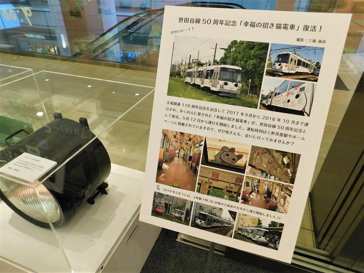 「幸福の招き猫電車」を紹介するパネル展示。左は、かつての車両(デハ70・80形)に取り付けられていた前照灯(「世田谷線にのって展」会場にて)