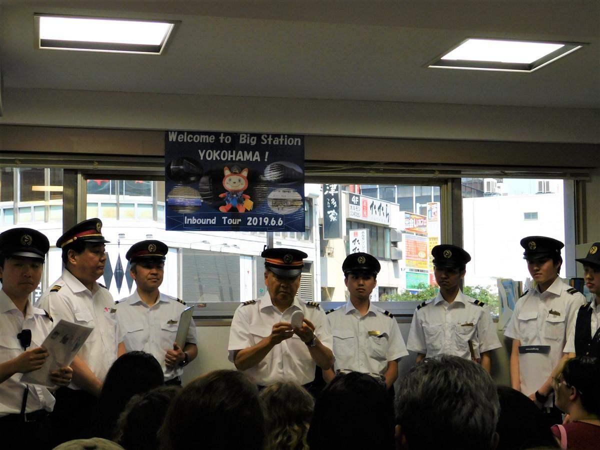 今回のプログラムを担当した駅員の皆さん。中央は通訳機を手に挨拶する臼井駅長。歓迎メッセージなどが英語で流れると、より大きな拍手が起きました