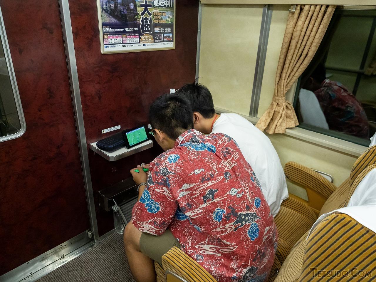 ドリームカーで音を消して「NintendoSwitch」をプレイする2人。昭和の中で令和を楽しんでいました