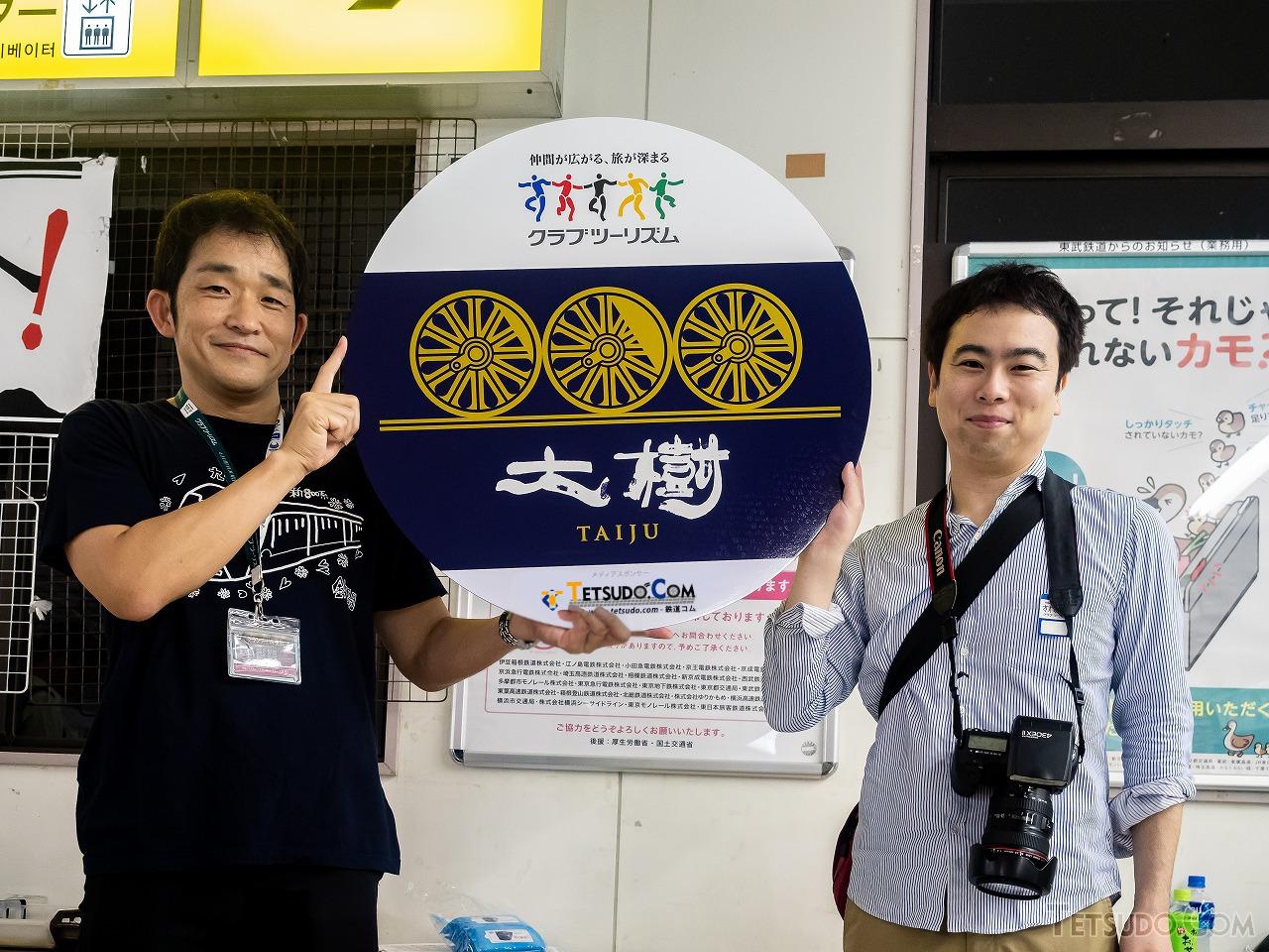 鉄道コム20周年を記念して制作されたオリジナル「大樹」ヘッドマークを持つクラブツーリズムの大塚雅士氏(左)。右は本媒体編集長の松岡孝昌