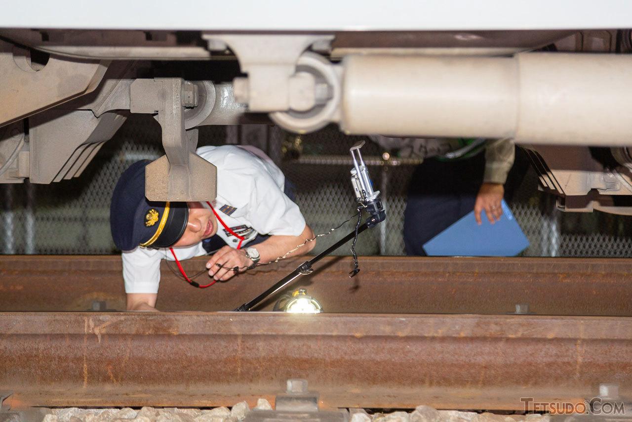 車掌がスマートフォンのカメラで台車を撮影している様子。伸縮棒も活用し、各機器の間近から撮影していました