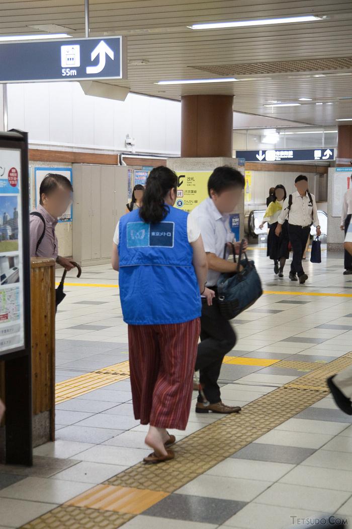 新木場駅の人ごみの中で、アプリを使って歩く高橋史月さん