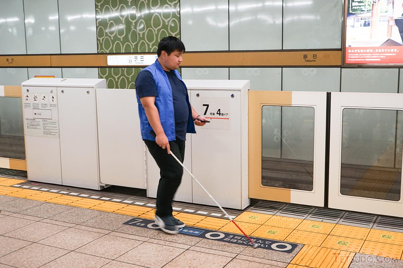 アプリを使いながら、辰巳駅のプラットフォームを歩く松尾政輝さん
