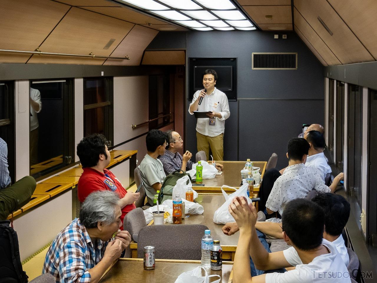 松岡編集長による鉄道コム20周年記念ツアー参加者限定の車内イベントがスタート。「折角参加してくださった方々に仲良くなってほしい」と知恵を絞ったそう