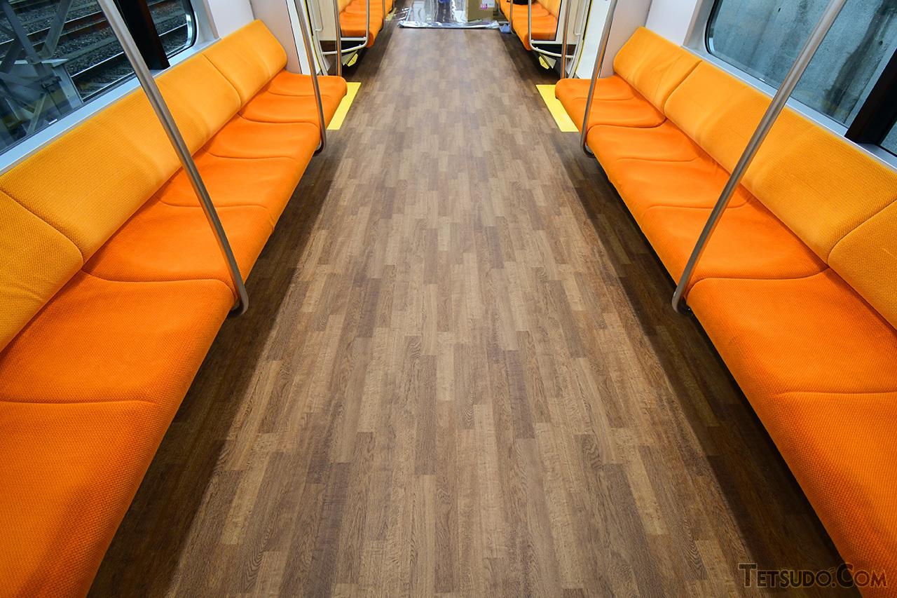 床面は木目調に。オレンジ色の座席モケットとあわせ、温かさを演出しています