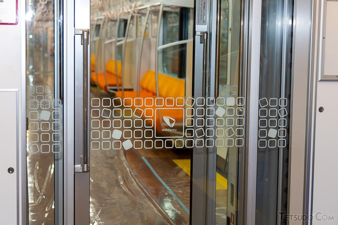 車両間の扉にも強化ガラスを採用。小田急グループのブランドマークが描かれています