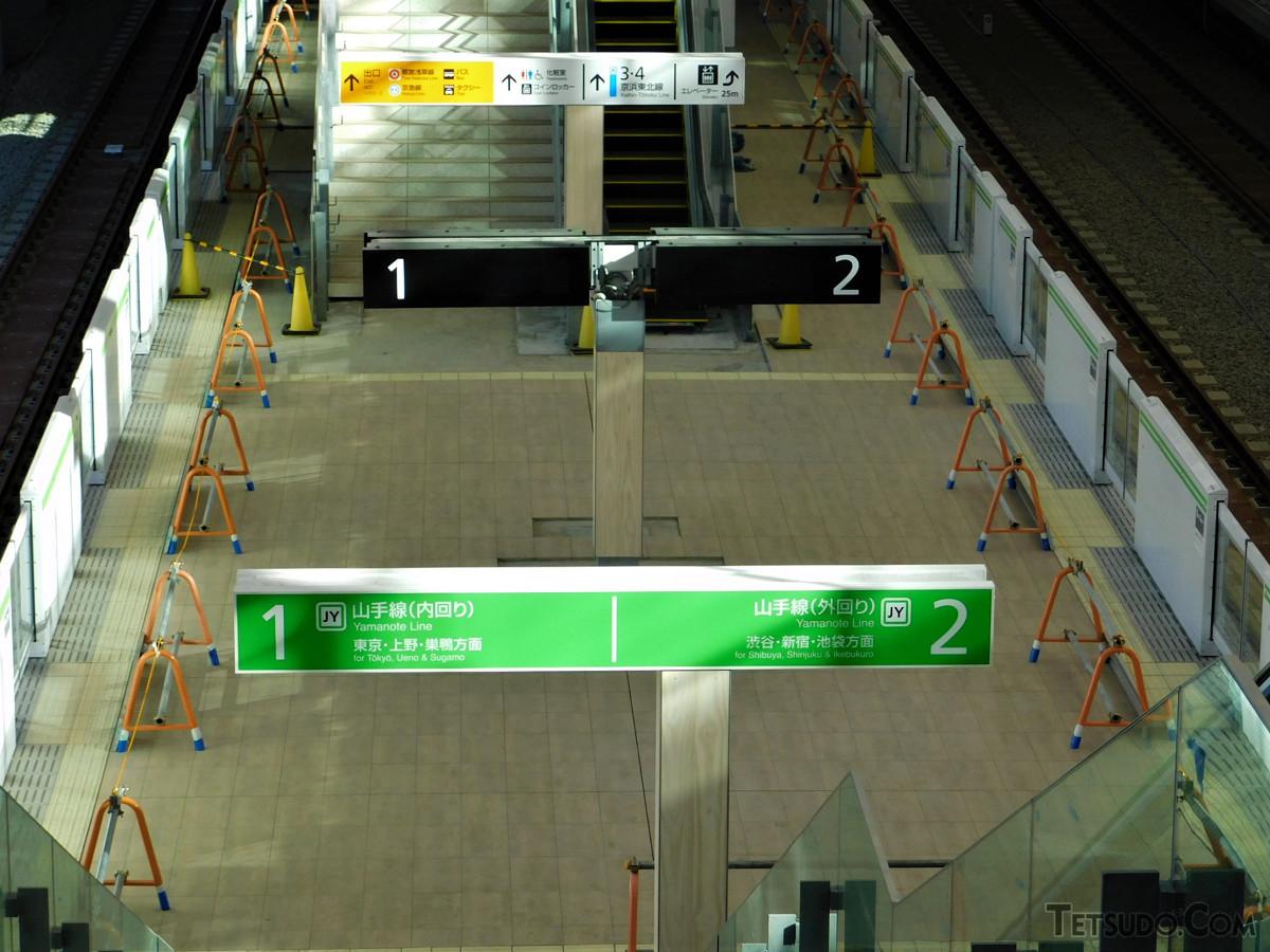 西側、山手線ホーム(1・2番線)。柱に取り付ける形の番線表示・発車標が特徴的です。床面は、木目調のタイルが使われています