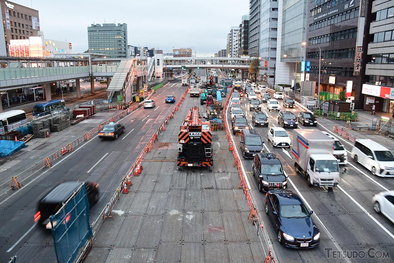 新横浜駅前の円形歩道橋から羽沢横浜国大駅方向を見た写真。中央の覆工板の下で、新横浜線の工事が進められています