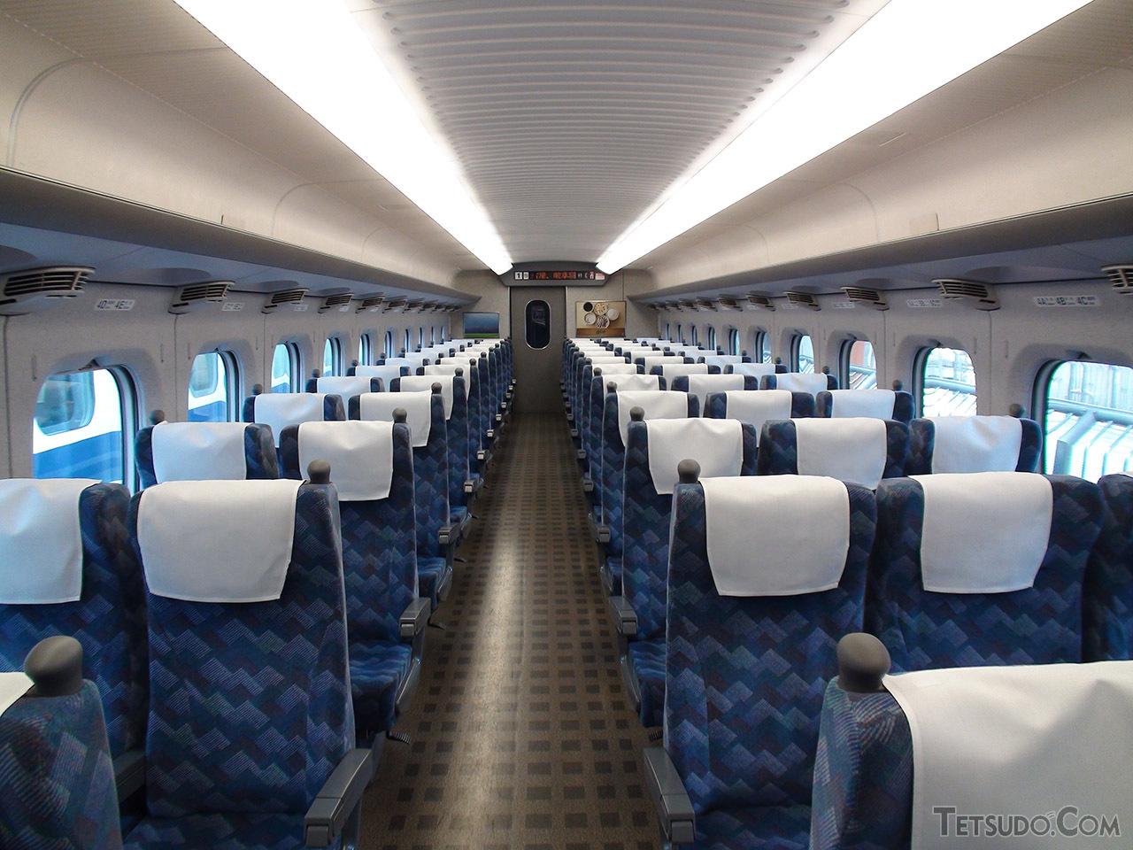 ブルー系のシートモケットと、シンプルな直接照明で明るい雰囲気になったC編成の普通車。空調の吹き出し口も、天井付近に設けられていた300系は空調の効きが悪いと言われたことから各座席の上に設置された