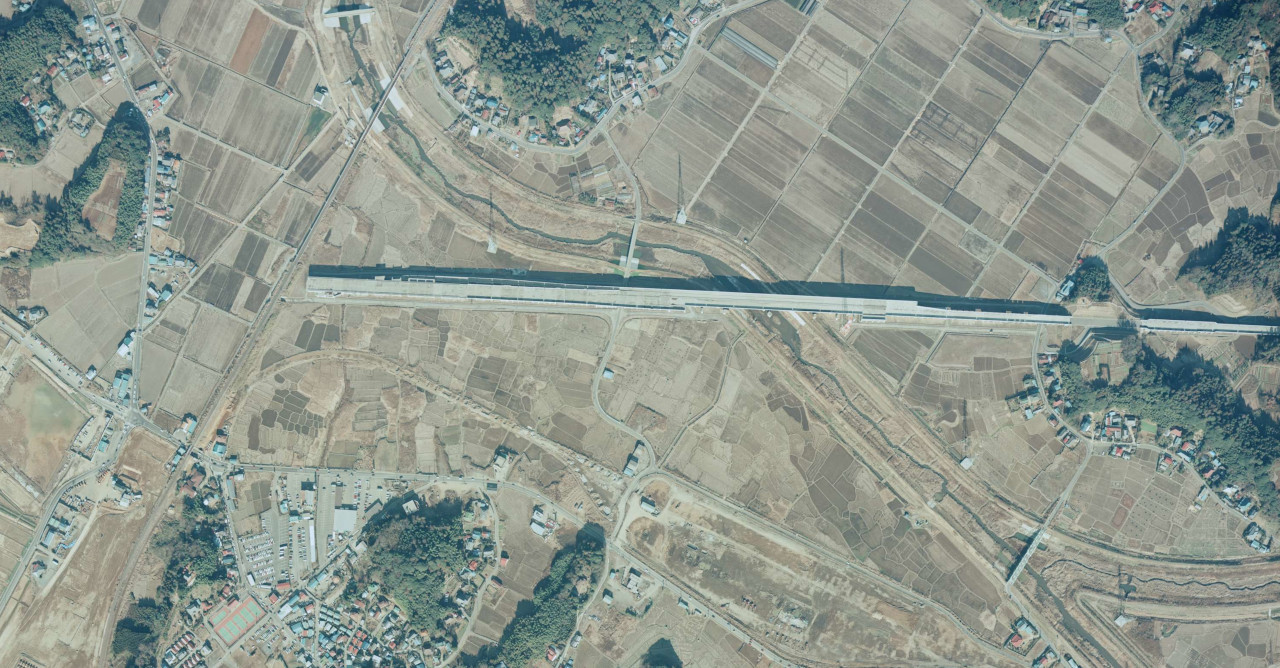 1985年当時の、成田市土屋付近の成田新幹線高架橋。本線から分岐する、現在のアプローチ線が写されています(国土地理院の空中写真(1985年撮影)を加工