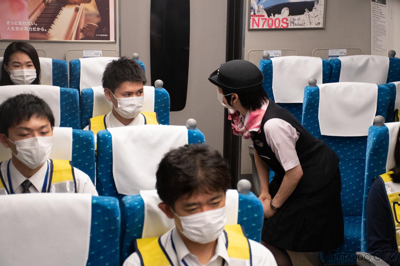 列車の運転見合わせ放送が流れた訓練列車の車内。ジェイアール東海パッセンジャーズの係員が、乗客(役の社員)に状況を説明していました