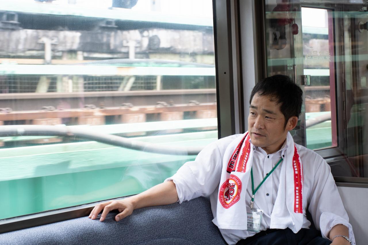 クラブツーリズムの大塚雅士さん。今回のツアーの仕掛け人で、車内放送も担当した。