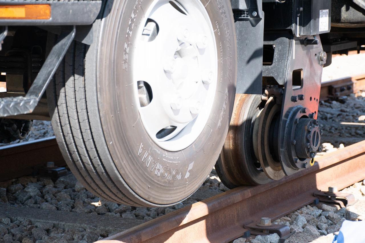 架線作業車の床下をアップ。鉄車輪がレールの上に乗っており、前タイヤは地面から離れているのがわかる。
