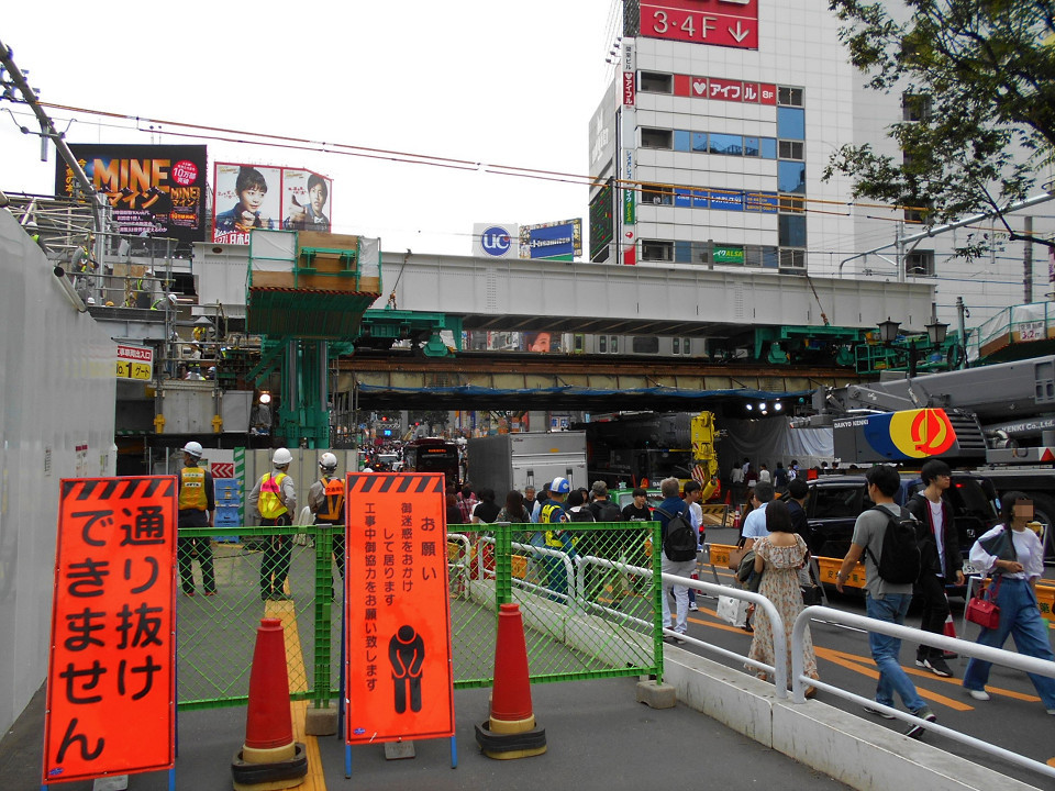 旧大山街道を行き交う人や車の様子。片側の車線には、大がかりな工事用車両が並び、その車列と仮の歩道との間に確保した車道を車がすれ違う状態になりました。写真奥側がスクランブル交差点(渋谷駅前交差点)です。