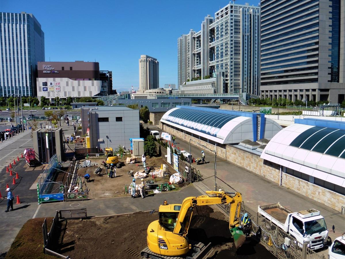 東京テレポート駅の駅舎(右側)と、工事が進む駅前の様子。左側の箱状の構造物は、増設工事中の改札外エレベーター。地上部と地下の改札階を結びます。