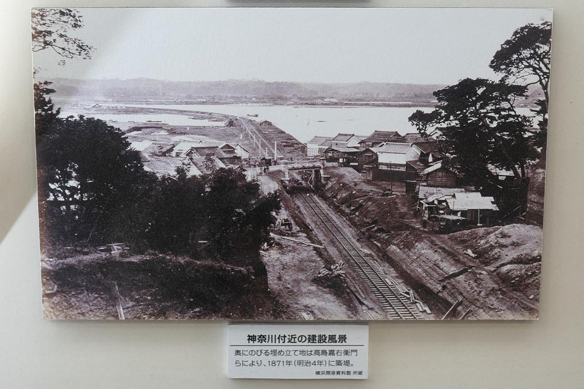 神奈川付近の建設風景。現在の横浜駅付近にあった入江を埋め立てる工事を兼ね、線路が敷かれました。埋立地の造成は、当地で材木や旅館を業としていた高島嘉右衛門が請け負いました。(桜木町駅で展示中のパネル写真より)