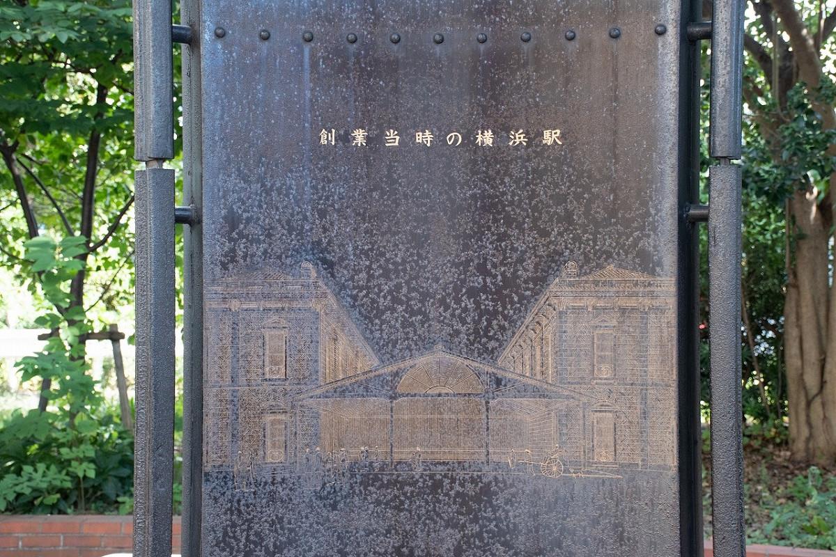 桜木町駅の南側に建つ「鉄道創業の地 記念碑」。1967年10月13日に設置されました。3つの面を組み合わせた三角柱状の碑で、1つは創業当時の横浜駅の様子、ほかの面には品川~横浜間の仮開業当時の時刻表などが刻まれています。