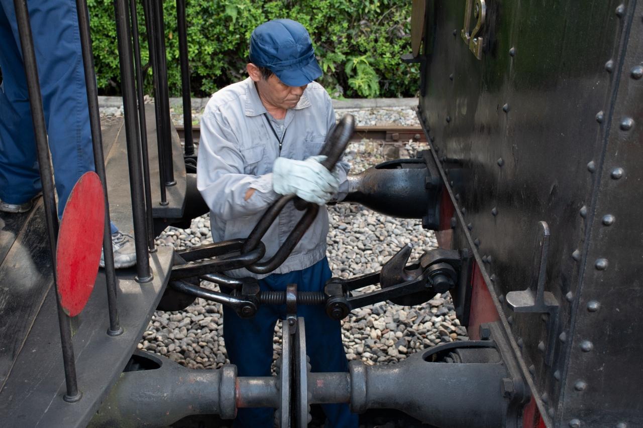 現代の日本では貴重な螺旋輪環連結器の連結シーン。下にある鎖のネジを締め付けた上で、作業員が手に持っている鎖を相手車両に引っ掛けます