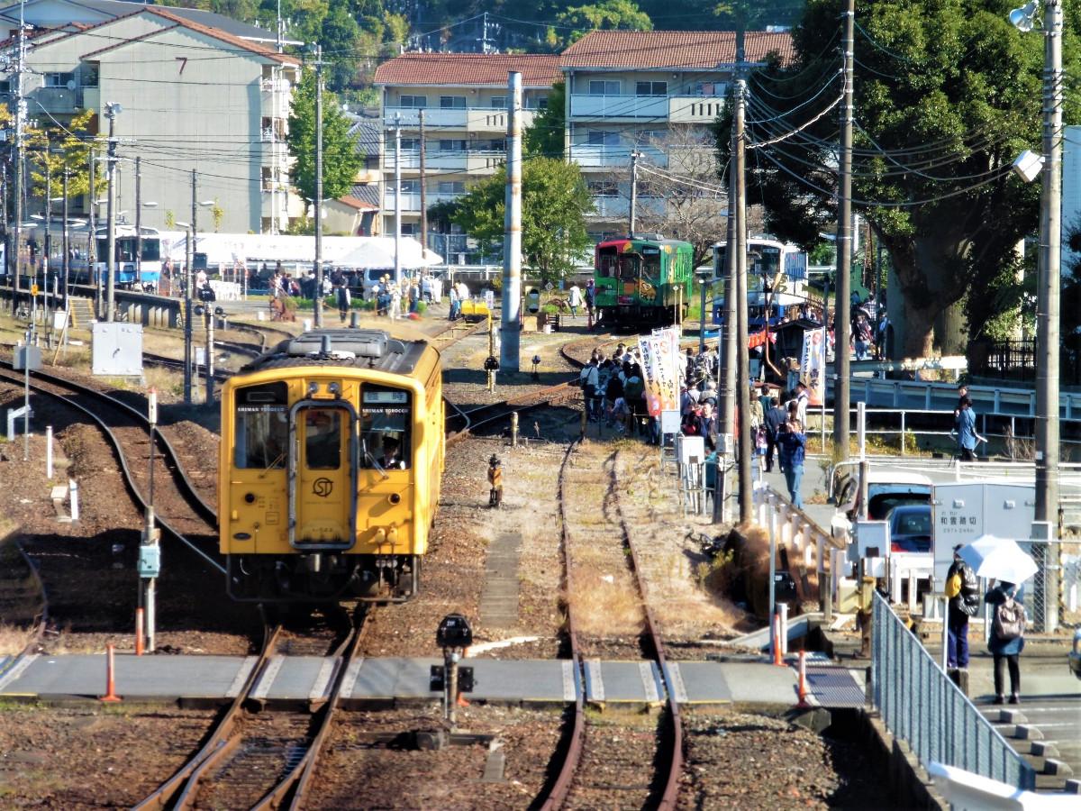 会場の宇和島運転区と、同運転区を宇和島駅に向けて発車した予土線の観光列車「しまんトロッコ」。しまんトロッコは、後方右の2つの列車とあわせて称される「予土線3兄弟」の1つで、デビューした順により「長男」と位置付けられています。