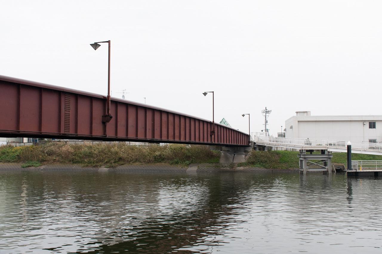 海老取川に架かる人道橋、天空橋(左)。写真奥の方向が羽田空港です。かつて空港島へ乗り入れていた際の鉄道橋も、天空橋とほぼ同じ位置にありました。1987年ごろまでは残存していましたが、空港線延伸と前後して、現在の天空橋へと架け替えられました