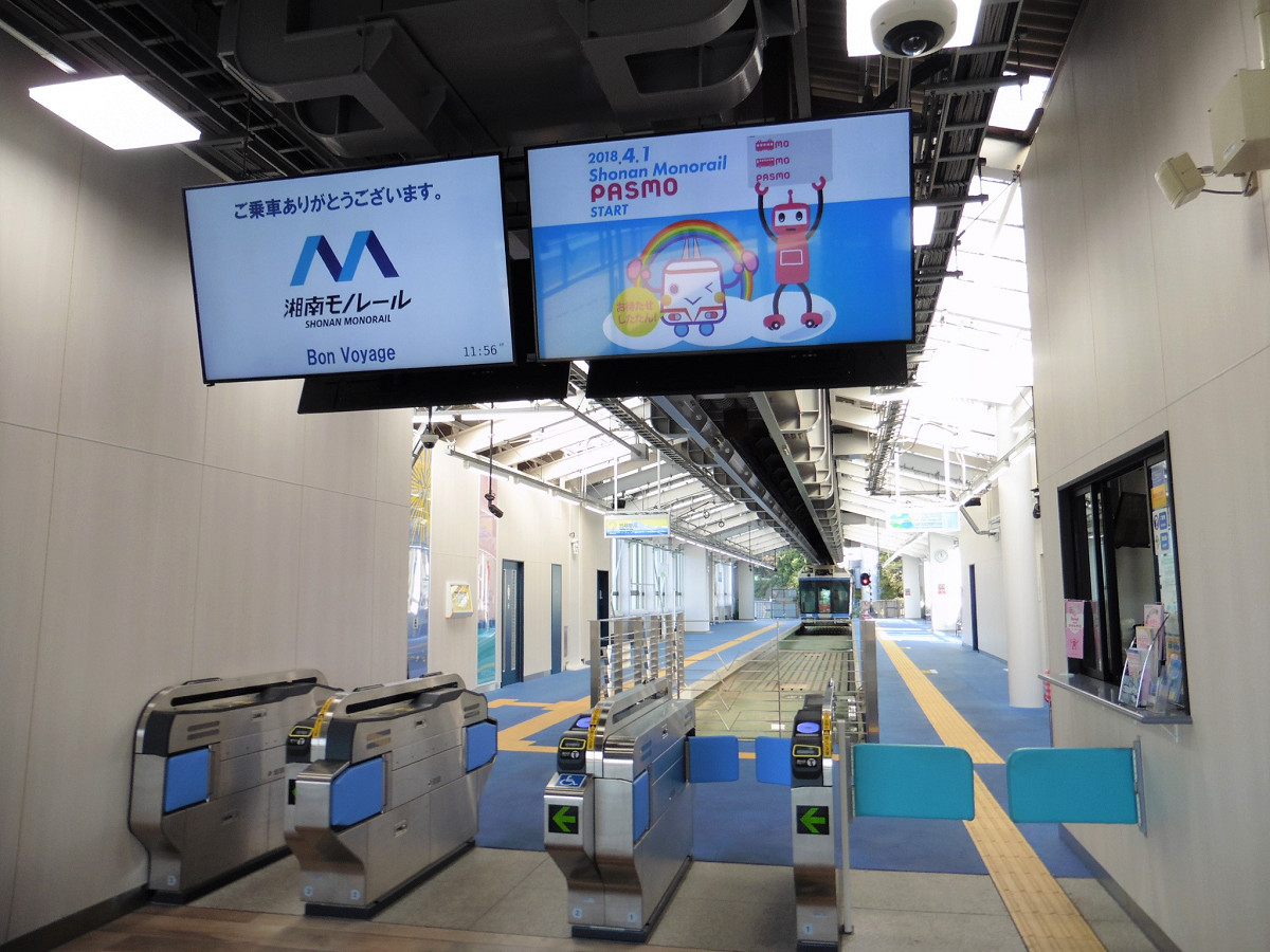 改札口の様子。湘南モノレールでは、2018年4月1日に交通系ICカードが導入され、ICカード対応の自動改札機の使用も同日始まりました。改札機上には、デジタルサイネージのディスプレイも新たに設置。左の画面には、4月から使われている新デザインのロゴマークが表示されています。