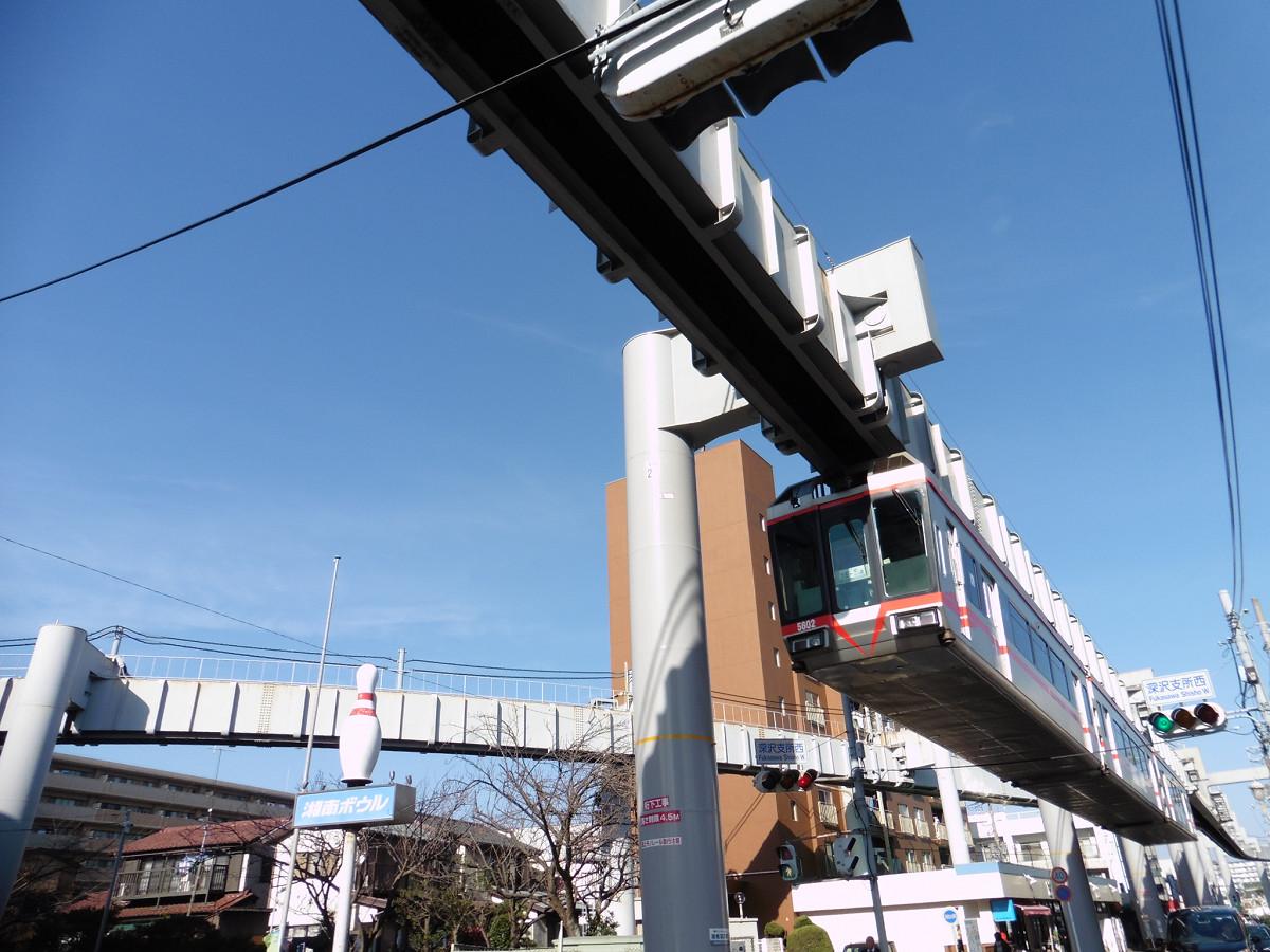 湘南深沢駅付近を走る5000系。2004年に写真の「湘南レッドライン」(5601編成)がデビューし、2016年までに計7編成が導入されました。湘南モノレールの営業用車両は、すべて5000系になっています。左側のレール桁は、湘南モノレール車両基地に通じる車庫線です。