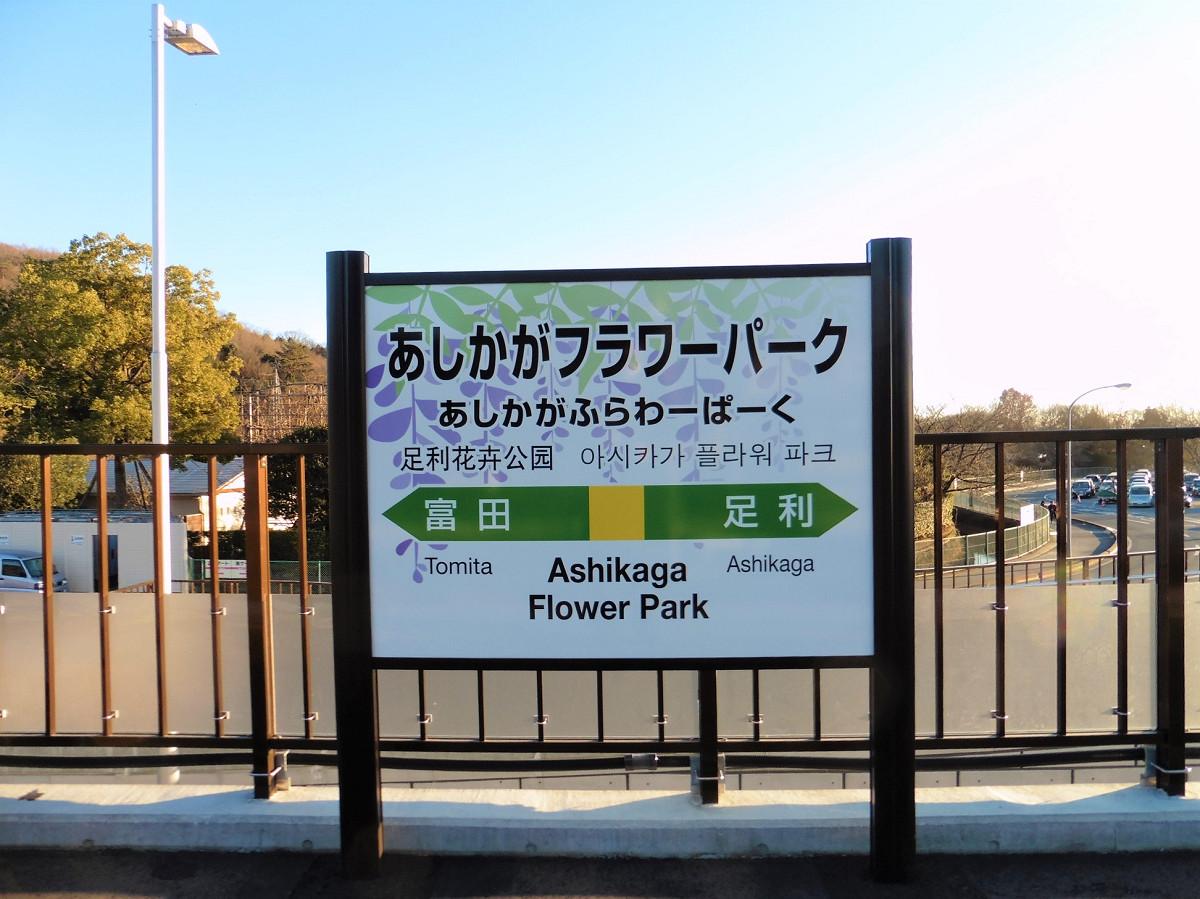 あしかがフラワーパーク駅の駅名標。フラワーパークを代表する藤の花がデザインされ、目を惹きます。東隣の富田駅までは0.9キロ、西隣の足利駅までは6.2キロの位置に開設されました。