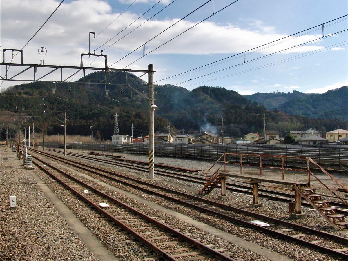 葛生駅構内。石灰やセメントの輸送拠点だったため、構内は広く、かつては左奥に向け、東武会沢(あいさわ)線・大叶(おおがの)線などの貨物線も延びていました。右はかつての貨物ヤード。跡地活用として、現在はメガソーラー施設が稼働しています。