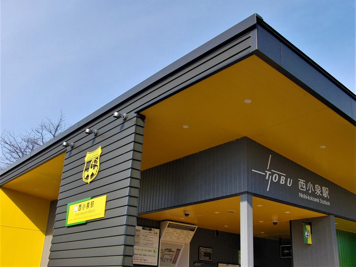 西小泉駅駅舎。天井や壁面に黄色が使われ、駅のシンボルマークなども黄色が使われています。シンボルマークは、ブラジルの国鳥がモチーフです。