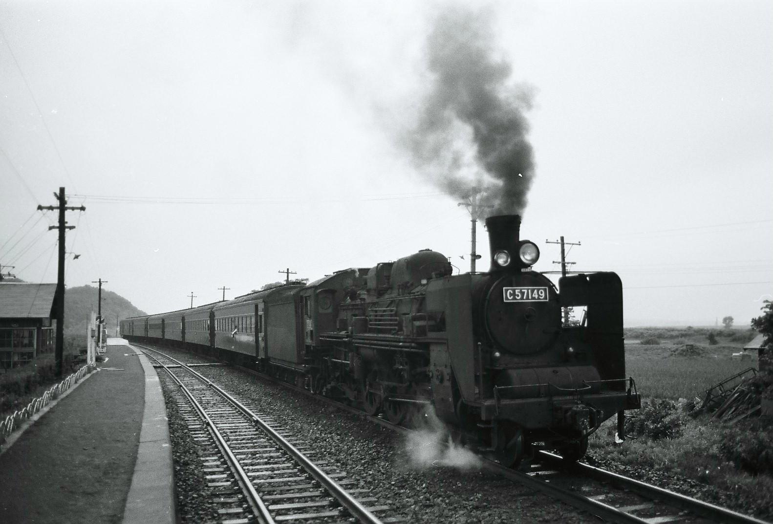 1973年7月、室蘭本線の栗丘駅で撮影された旅客列車。けん引機は、C57形の149号機です。煙突前には、前照灯が2つ。向かって左側の小さな補助灯は、交流電化区間を有する地域独特の装備です。前照灯が球切れした際に電球を交換する際、20000ボルトの高電圧となっている交流電化区間では、架線に触れなくとも感電する恐れがありました。もちろん夜間に前照灯非点灯で走ることは認められていないため、このような補助灯を設置して、万が一の対策としていたそうです。前照灯の下には、「架線注意」の表記も見られます。149号機は、1974年に廃車。車体も解体されてしまいますが、第1動輪のみが保存され、現在は新潟県の新津駅付近で展示されています。