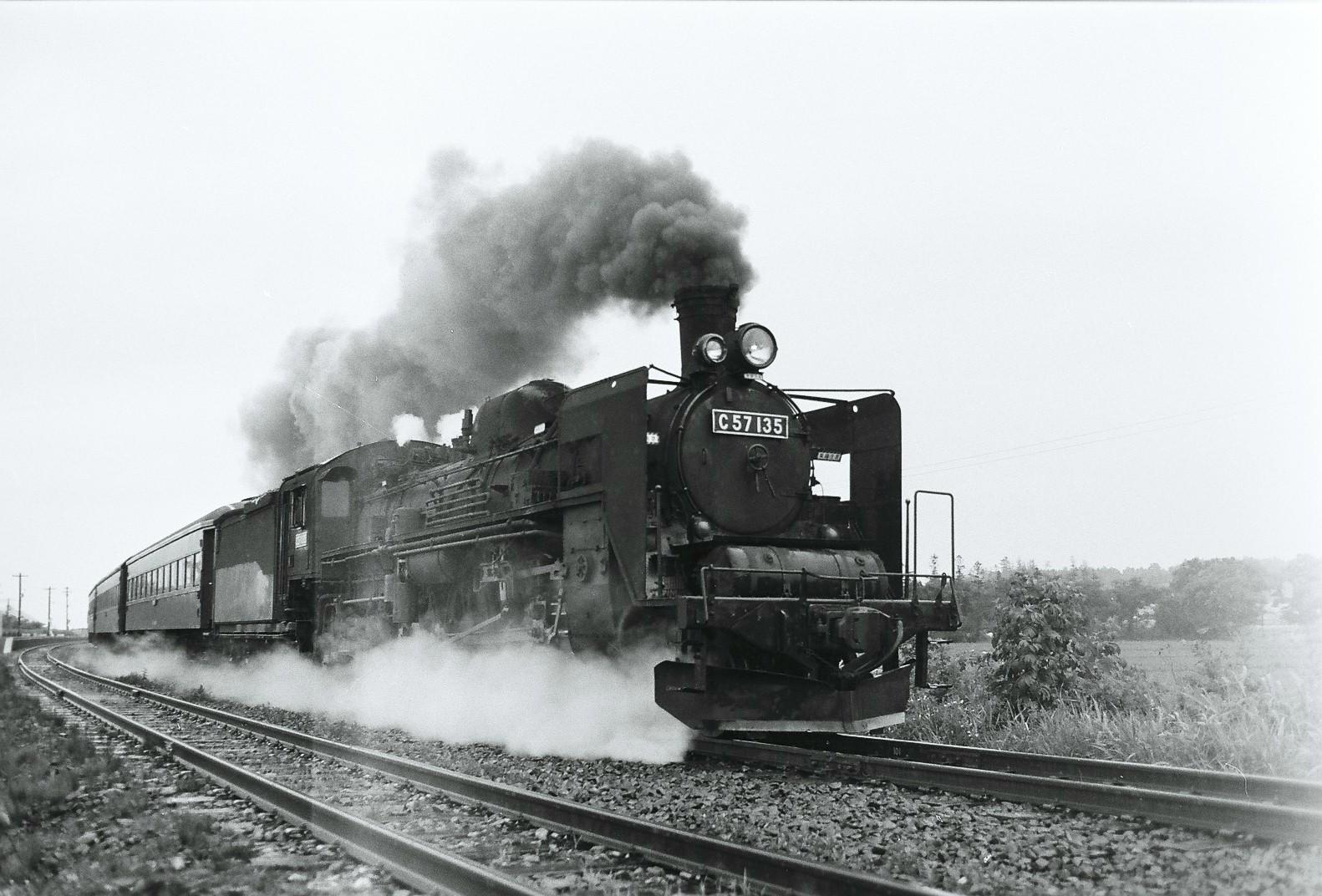 前の写真と同じ、1973年7月に室蘭本線栗丘駅付近で撮影された、C57形135号機けん引の列車。岩見沢第一機関区に所属する機関車です。この写真が撮影された2年後の1975年12月14日、国鉄最後の蒸気機関車けん引列車が室蘭本線室蘭~岩見沢間で運転されるのですが、この列車のけん引機に抜擢されたのが135号機でした。同機はこの経歴により、国鉄蒸機のマイルストーン的存在として、廃車後は交通博物館(東京都)に収蔵、展示保存されます。同館の閉館後は、2007年に開館した鉄道博物館(埼玉県)に移され、現在も同館「車両ステーション」の目玉展示の一つとして、来場者の注目の的となっています。C57形135号機けん引による最後の蒸気機関車けん引旅客列車運転後も、国鉄蒸機の歴史は少しだけ続きました。1975年12月24日、D51形のけん引による、最後のSL貨物列車が夕張線(当時)で運転され、営業線上のSL「列車」は全廃。翌1976年の3月、追分機関区の9600形の入換仕業が消滅したことにより、国鉄線上から保存機以外の蒸気機関車の火は消えることとなりました。