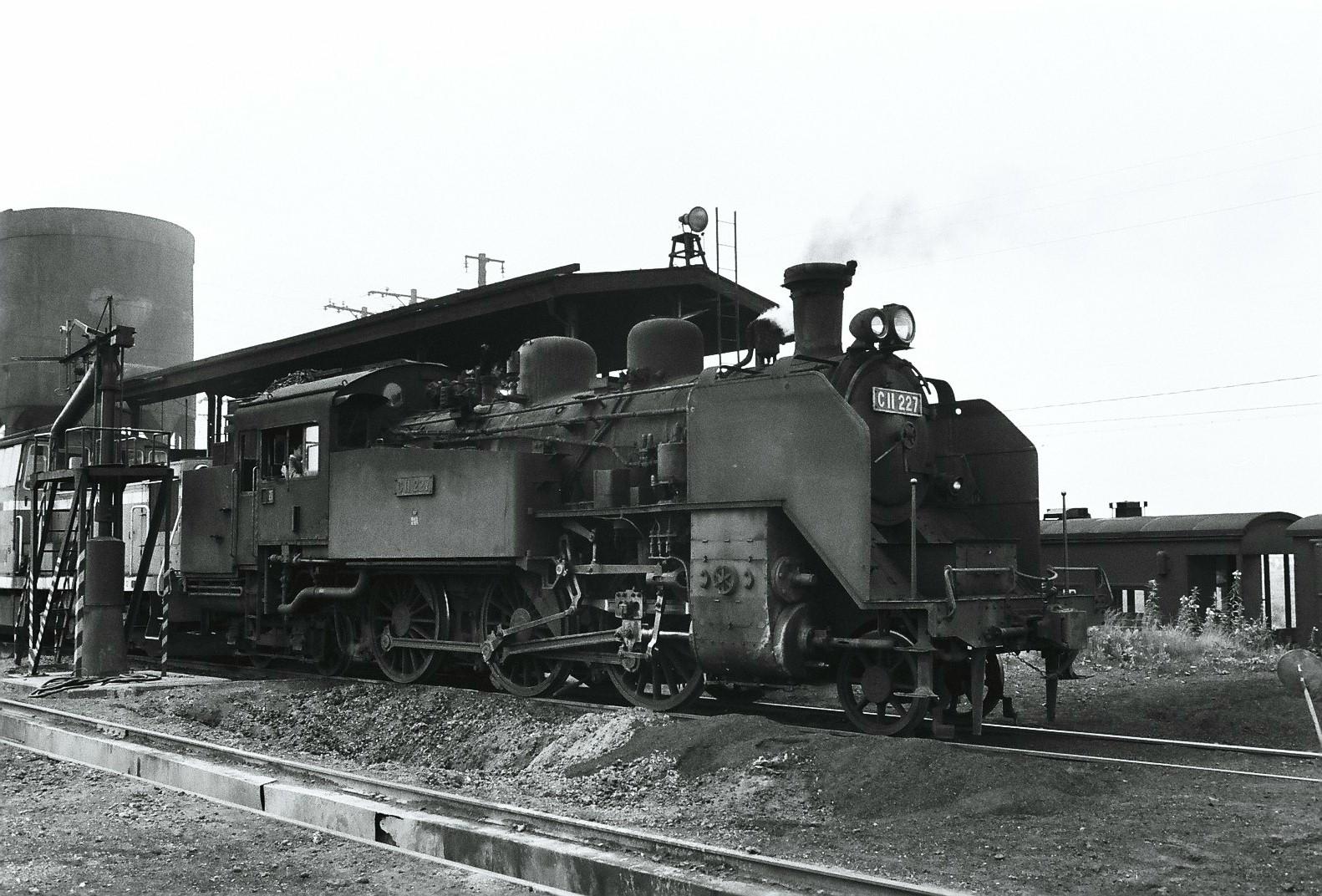苫小牧機関区で休息を取るC11形227号機。1973年7月の撮影です。苫小牧機関区に所属していた同機は、当時は日高本線や富内線などで運用されていました。撮影された当時には、現在は東武鉄道のSL「大樹」けん引機として活躍しているC11形207号機も、同じ苫小牧機関区に所属していました。写真の227号機は、撮影から2年後の1975年に廃車されますが、そのまま大井川鉄道(現:大井川鐵道)に譲渡されました。ボイラーを交換するなど手は加えられているものの、現在もSL急行「かわね路」などのけん引機として、製造から70年以上が経過した現在も現役です。