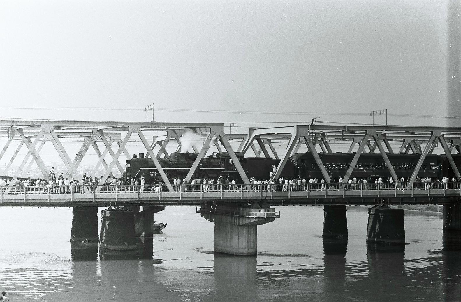 1972年の10月14日と15日、日本の鉄道開業100周年を記念して、「鉄道百年記念列車」が汐留~東横浜間で運転されました。かつての三等車を模して赤帯を入れた客車を、C57形7号機がけん引するというもので、京浜間では久しぶりのSL列車運転ということもあり、かなりの人出があったようです。こちらの写真は、10月15日に東海道本線の六郷川橋りょうで撮影されたもの。鉄橋の上、線路敷地内で撮影する多くのファンが写っています。現在は線路内に立ち入っての撮影は絶対に許されるものではありませんが、当時は規制も緩く、列車妨害にならない範囲であれば黙認されていたようです。
