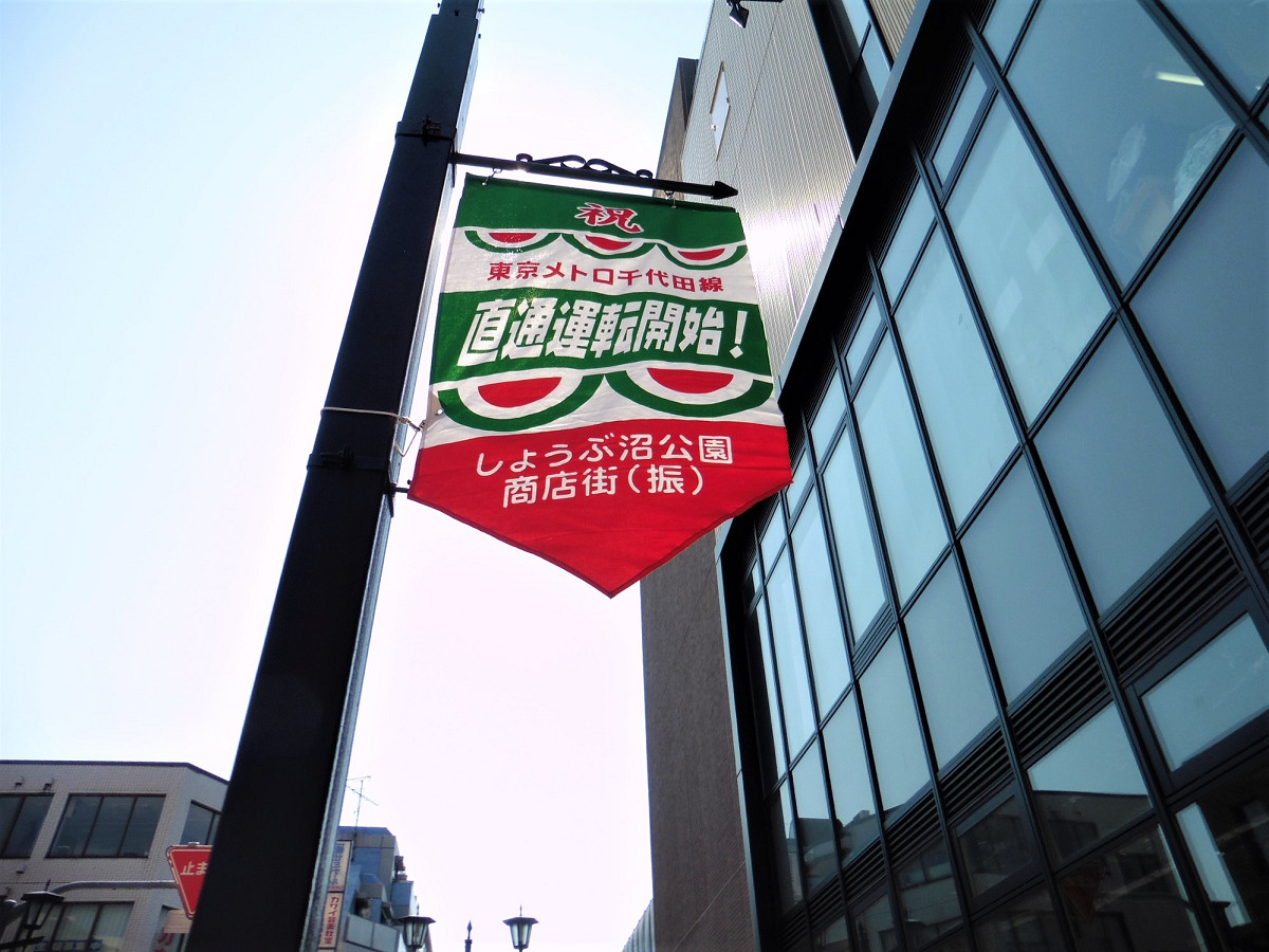 北綾瀬駅近接の商店街では、直通運転開始を祝す旗も。15日の式典では、直通運転のスタートを新たな街の始まりととらえる趣旨の話もありました。