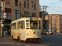 road, building, outdoor, street, land vehicle, tram, city, vehicle, transport, bus, text, streetcar, driving, traveling, busy, train, day