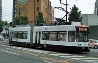 road, street, outdoor, building, train, bus, city, land vehicle, text, tram, vehicle, driving, streetcar, traveling, way, past, busy