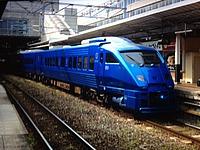 train, track, building, blue, transport, outdoor, rail, land vehicle, vehicle, station, platform, pulling, railway, traveling, rolling stock, locomotive, moving, railroad