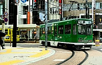 building, text, outdoor, street, train, green, land vehicle, vehicle, tram, city, streetcar, way, busy